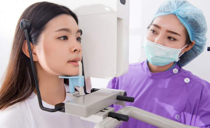 A dentist giving a girl a digital x-ray