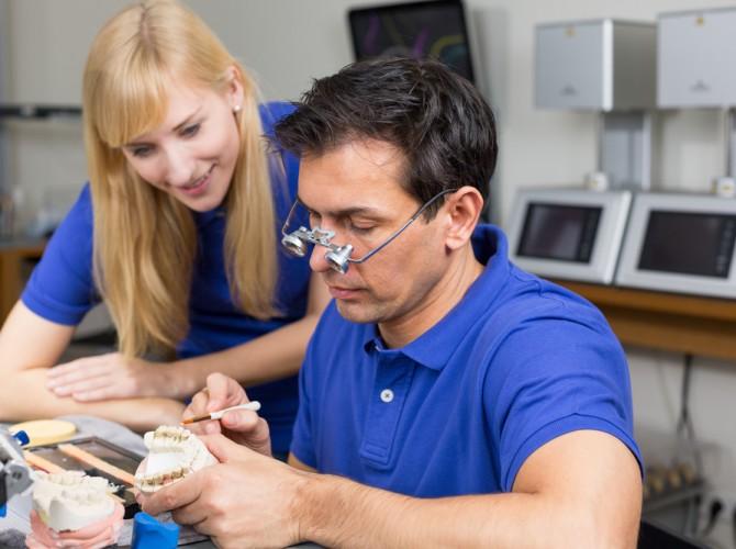 Denturist working on Dentures while woman Dentist observes